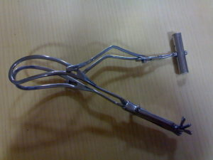 Das's long curved delivery forceps with axis traction devices in place